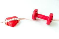 Röda hantlar för Closeup med att mäta bandet runt om röd hjärta Fotografering för Bildbyråer