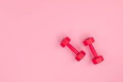Röda hantlar för kondition som isoleras på rosa bakgrund Royaltyfri Foto