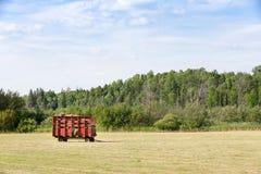 Röda Hay Wagon i ett lantgårdfält Royaltyfria Foton