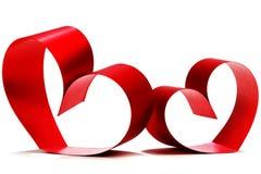 Röda hjärtor av bandpilbågen Royaltyfria Bilder