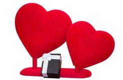 Röda hjärtor för mjuk sammet och svart gåvaask på vit bakgrund Royaltyfri Foto