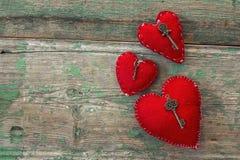 Röda hjärtor med antika tangenter på gamla målade träbräden Mig Arkivbild