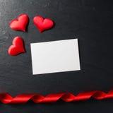 Röda hjärtor med postcardonstenbakgrund Arkivfoto
