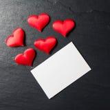 Röda hjärtor med postcardonstenbakgrund Arkivfoton