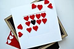 Röda hjärtor med ramen i den vita bakgrunden Arkivfoto