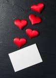 Röda hjärtor med vykortet på stenbakgrund Arkivbilder