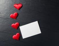 Röda hjärtor med vykortet på stenbakgrund Arkivfoto