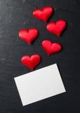 Röda hjärtor med vykortet på stenbakgrund Royaltyfri Foto