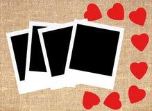 Röda hjärtor och fotokort på bakgrund för säckkanfassäckväv Royaltyfria Foton