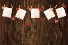 Röda hjärtor och mellanrumspapper med en bild som hänger på ett rep V Arkivfoton