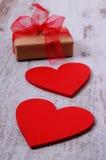 Röda hjärtor och slågen in gåva för valentindag på den gamla trätabellen Royaltyfri Bild