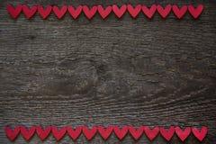 Röda hjärtor ordnas horisontellt på överkanten och de nedersta kanterna av en träbrun träplanka valentin för form för korthjärtaf royaltyfri foto