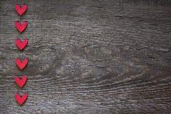 Röda hjärtor ordnas vertikalt till vänstersidan på ett träbrunt bräde valentin för form för korthjärtaförälskelse royaltyfri bild