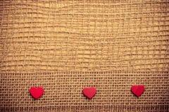 Röda hjärtor på abstrakt torkdukebakgrund Arkivfoto