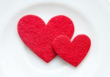 Röda hjärtor på en pläteranärbild. Valentin dag royaltyfri bild