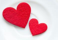 Röda hjärtor på en pläteranärbild. Valentin dag arkivfoto