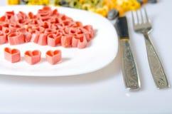 Röda hjärtor som göras av pasta på en vit platta Royaltyfri Fotografi