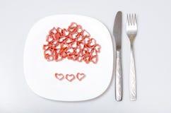 Röda hjärtor som göras av pasta på en vit platta Royaltyfri Bild