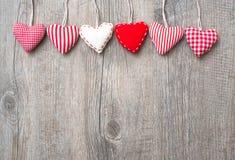 Röda hjärtor som hänger över wood bakgrund arkivbilder