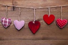 Röda hjärtor som hänger i en linje för valentin Daecoration Arkivfoto