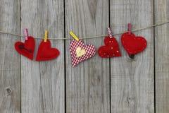 Röda hjärtor som hänger på klädstreck Royaltyfria Bilder