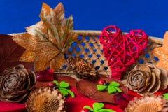 Röda hjärtor, torkad lövverk och sörjer kotten Julgarnering på blåttbakgrund arkivfoton