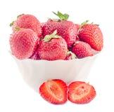Röda jordgubbar med gröna sidor i en vit bunke som isoleras Arkivfoton