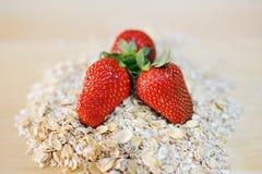 Röda jordgubbar på en hög av havren flagar Arkivbild