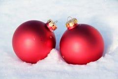 Röda julbollar i snön arkivbilder