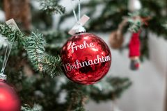 Röda julbollar med den wrting 'Frohen Weihnachten 'på den Weihnachtskugel mit Frohe Weihnachten royaltyfri bild
