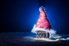Röda julbollar med 2018 nummer och Santa Claus hatt på naturlig snöbakgrund Begrepp 2018 för lyckligt nytt år kopiera avstånd sel Royaltyfria Foton