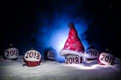 Röda julbollar med 2018 nummer och Santa Claus hatt på naturlig snöbakgrund Begrepp 2018 för lyckligt nytt år kopiera avstånd sel Arkivbild