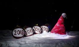 Röda julbollar med 2018 nummer och Santa Claus hatt på naturlig snöbakgrund Begrepp 2018 för lyckligt nytt år kopiera avstånd sel Royaltyfria Bilder