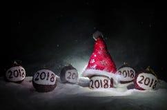 Röda julbollar med 2018 nummer och Santa Claus hatt på naturlig snöbakgrund Begrepp 2018 för lyckligt nytt år kopiera avstånd sel Arkivfoto