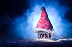 Röda julbollar med 2018 nummer och Santa Claus hatt på naturlig snöbakgrund Begrepp 2018 för lyckligt nytt år kopiera avstånd sel Royaltyfri Foto