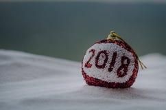 Röda julbollar med 2018 nummer och Santa Claus hatt på naturlig snöbakgrund Begrepp 2018 för lyckligt nytt år kopiera avstånd sel Royaltyfri Bild