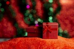 Röda julgåvaaskar på röd matta och grön trädbakgrund royaltyfri foto