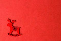 Röda julhjortar sned stol på en brandbakgrund, träecogarnering, leksak Royaltyfri Foto