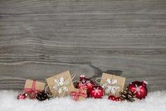 Röda julklappar som slås in i naturligt papper på gammal trägr Arkivfoto