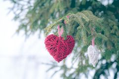 Röda julprydnader, hjärta, på ett kort för hälsning för glad jul för julgran Tema för vinterferie royaltyfri bild