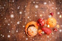 Röda julprydnader och apelsin på träferiebakgrund Sammansättning för Xmas och för lyckligt nytt år arkivbild