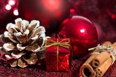 Röda julprydnader och kanelbrun kryddastång royaltyfria bilder