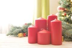 Röda julstearinljus på den vita träplankan mot julträd i vardagsrum royaltyfri foto