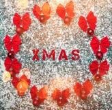Röda julstruntsaker med bandpilbågar och xmas-etikett på vintervitbakgrund arkivbilder