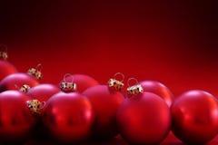 Röda julstruntsaker på röd bakgrund, kopieringsutrymme Arkivbild