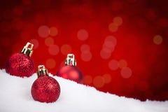 Röda julstruntsaker på snö med en röd bakgrund Arkivbild
