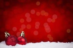 Röda julstruntsaker på snö med en röd bakgrund Arkivfoto