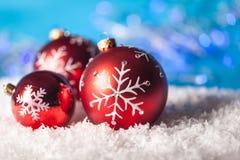 Röda julstruntsaker på snönärbild royaltyfri bild