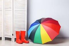 Röda kängor med paraplyet Arkivbild