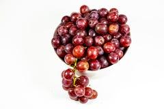 Röda kärnfria druvor i en djup vit bunke på en vit saga som väntar för att ätas royaltyfria bilder